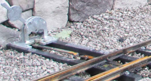 It is perfectly feasible, and normal practice on miniature and in places full size railways, to be able to trail through a point. Locking is only needed for travel in the facing direction to ensure there isn't a derailment and to put you on the correct route. A spring mechanism in the operating bar is all that's needed. The photo shows a hand operated point at Abbeydale's Woodside Carriage depot, but the principle is the same and used on our powered pointwork.